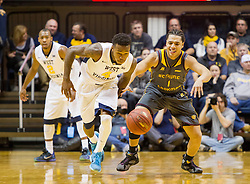 Nov 23, 2015; Morgantown, WV, USA; West Virginia Mountaineers guard Daxter Miles Jr. steals the ball from Bethune-Cookman Wildcats guard Josue Salaam during the first half  at WVU Coliseum. Mandatory Credit: Ben Queen-USA TODAY Sports