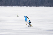 A person glides by on a skate-adapted windsurfing board as participates prepare their iceboats for competition in the North American Championship DN Ice Sailing Regatta on frozen Lake Monona in Madison, Wis., during winter on Feb. 25, 2016. (Photo by Jeff Miller, www.jeffmillerphotography.com)