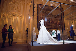 Windsor, UK. 28th February, 2019. Exhibition curator Caroline de Guitaut (l) observes HRH Princess Eugenie's wedding dress, created by Peter Pilotto and Christopher De Vos of the British-based label Peter Pilotto, and Mr Jack Brooksbank's morning suit made by tailors at Huntsman on Savile Row, which go on display with other items from their wedding outfits at Windsor Castle in a special exhibition named 'A Royal Wedding: HRH Princess Eugenie and Mr Jack Brooksbank' from 1st March to 22nd April. Other items included in the exhibition include the Greville Emerald Kokoshnik Tiara, on public display for the first time, two diamond wheat-ear brooches, diamond and emerald drop earrings, Princess Eugenie's evening gown, HRH Princess Beatrice's blue dress by the London-based couture house Ralph & Russo and headpiece by British milliner Sarah Cant and a bridesmaid and pageboy outfit by London-based children's designer Amaia Kids.