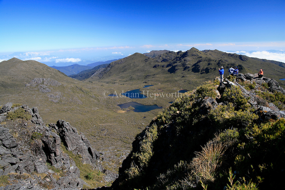 Tourists looking over Lakes Las Morenas from the summit of Mount Chirripo, Costa Rica's highest mountain (3820m). Chirripo National Park, Costa Rica.<br />