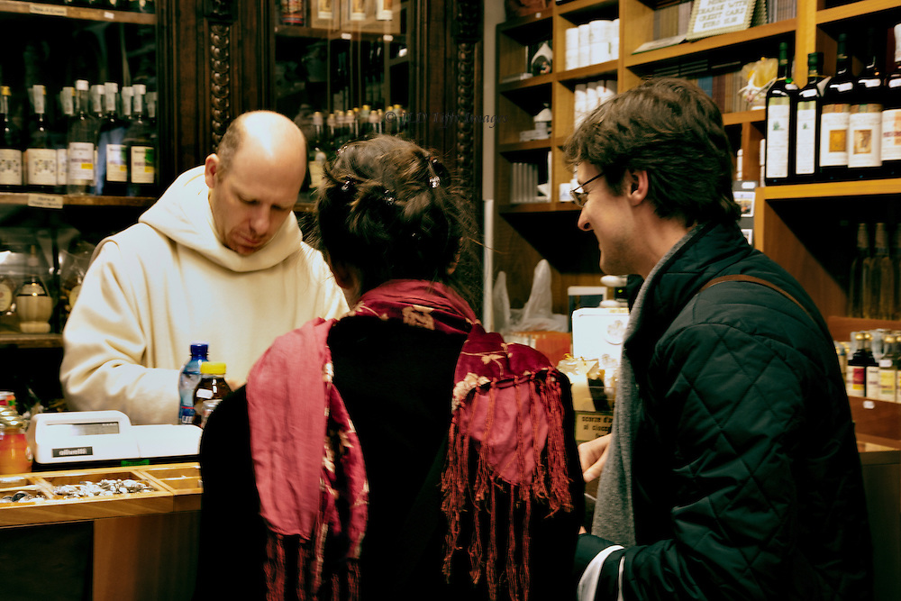 Inside the apothecary at San Miniato del Monte.  A Benedictine monk in charge sells items to a young French couple.