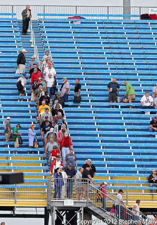 People head down the stairs as the grandstands are cleared due to a storm system moving in before the start of the IZOD IndyCar Iowa Corn Indy 250 auto race at the Iowa Speedway in Newton, Iowa on Saturday, June 23, 2012.