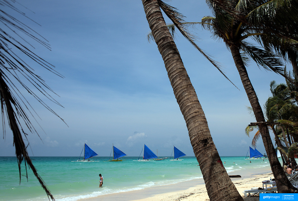 A beach scene by the pristine waters at White Beach on September 29, 2008 in Boracay Island, the Philippines. Photo Tim Clayton..Asian tourists at White Beach, Boracay Island, the Philippines...The 4 km stretch of White beach on Boracay Island, the Philippines has been honoured as the best leisure destination in Asia beating popular destinations such as Bali in Indonesia and Sanya in China in a recent survey conducted by an International Travel Magazine with 2.2 million viewers taking part in the online poll...Last year, close to 600,000 visitors visited Boracay with South Korea providing 128,909 visitors followed by Japan, 35,294, USA, 13,362 and China 12,720...A popular destination for South Korean divers and honeymooners, Boracay is now attracting crowds of tourists from mainland China who are arriving in ever increasing numbers. In Asia, China has already overtaken Japan to become the largest source of outland travelers...Boracay's main attraction is 4 km of pristine powder fine white sand and the crystal clear azure water making it a popular destination for Scuba diving with nearly 20 dive centers along White beach. The stretch of shady palm trees separate the beach from the line of hotels, restaurants, bars and cafes. It's pulsating nightlife with the friendly locals make it increasingly popular with the asian tourists...The Boracay sailing boats provide endless tourist entertainment, particularly during the amazing sunsets when the silhouetted sails provide picture postcard scenes along the shoreline...Boracay Island is situated an hours flight from Manila and it's close proximity to South Korea, China, Taiwan and Japan means it is a growing destination for Asian tourists... By 2010, the island of Boracay expects to have 1,000,000 visitors.