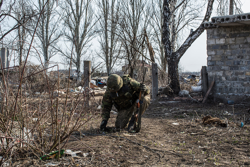 PISKY, UKRAINE - MARCH 20, 2015: Volodya, a fighter for the Dnipro-1 battalion, a pro-Ukrainian militia, stops to pick flowers in the heavily contested town of Pisky, Ukraine. CREDIT: Brendan Hoffman for The New York Times