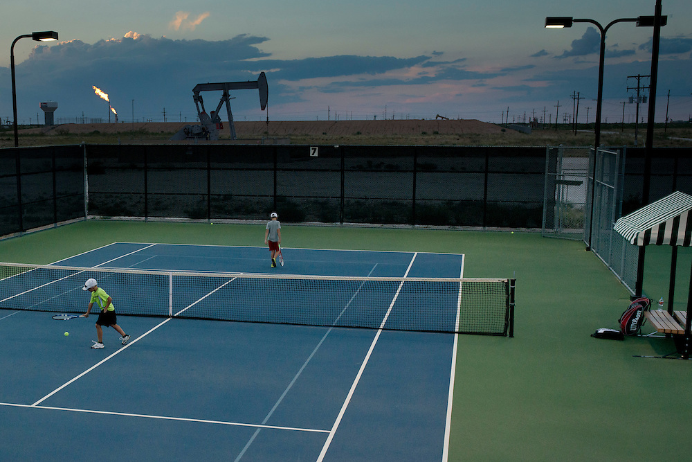 Conner Everett, 11, practices with his friend Caiden Reece at the Bush Tennis Center in Midland, Texas on August 12, 2014. (Cooper Neill for The New York Times)