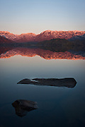 The waters of Sanabria Lake stand still as the light of dawn illuminates the mountains around it