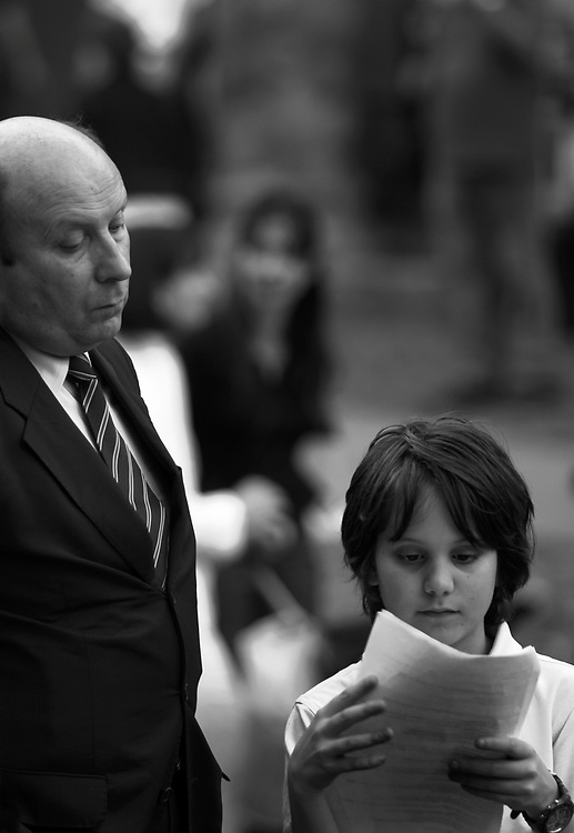 A father and son reading at a ceremony in Bologna.