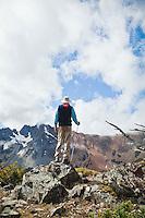 A man looking out on some mountains from atop a rocky outcrop.  Grasshopper Pass, Washington Cascades, USA.