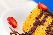 Piece of carrot cake decorated with chocolate and strawberry slices, macro.