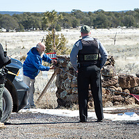 Cibola County Sheriffs Deputy Julian Armijo, left, and Undersheriff Mike Munk, right, watch the compounds caretaker Tom Briggs unlock the rope gate to the Aggressive Christianity Missions Training Corps (ACMTC) headquarters in Fence Lake Feb. 27th, 2019.