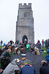 © Licensed to London News Pictures; 21/06/2020; Glastonbury, Somerset, UK. People welcome in the dawn on the Sunday of Solstice weekend on top of Glastonbury Tor after a night with some heavy rain and though low cloud and mist obscured the sunrise. This year due to the coronavirus Covid-19 pandemic and concerns over social distancing at gatherings of people, Stonehenge and Avebury where thousands of people usually gather to celebrate the summer solstice are closed to the public, with the solstice live streamed from Stonehenge. Glastonbury authorities had also asked people to refrain from coming to Glastonbury for the solstice but hundreds came with many staying the night on the Tor. Glastonbury Tor is a hill outside Glastonbury town, topped by the roofless St Michael's Tower, a Grade I listed building which is what remains of the Church of St Michael built in the 14th century. The entire site is managed by the National Trust and has been designated a scheduled monument. Photo credit: Simon Chapman/LNP.