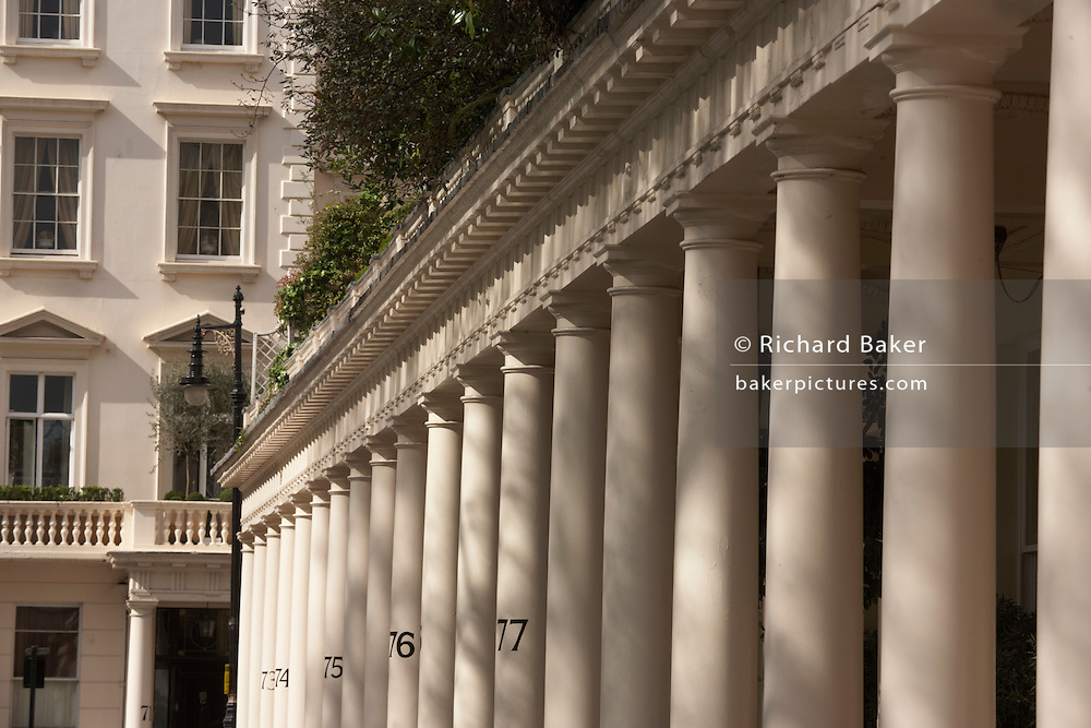 In a compressed perspective are the Doric pillars of London's famous Eaton Square. Bathed in mid-morning spring sunshine, shadows from nearby trees are cast over the cream-coloured pillars, some of which have the numbers of these exclusive and classically-designed properties in Belgravia. Shrubs and plants can be seen growing on the terraced balconies and  all the painted surfaces are pristine. Eaton Square is one of London's three garden squares built by Thomas Cubitt and the Grosvenor family when they developed the main part of Belgravia from 1826 until 1855. Belgravia attracts actors, politicians, ambassadors, big-budget bankers, traders and Prime Ministers like Neville Chamberlain and Stanley Baldwin at number 93.