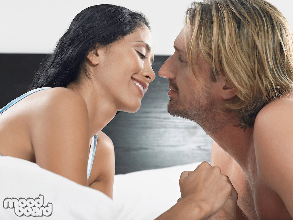 Couple about to kiss on bed head and shoulders