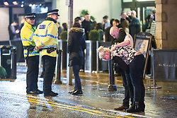 """© Licensed to London News Pictures . 20/12/2014 . Manchester , UK . A woman vomits in to a gutter on Deansgate , as a man comforts her . """" Mad Friday """" revellers out in the rain and cold in Manchester . Mad Friday is typically the busiest day of the year for emergency services , taking place on the last Friday before Christmas when office Christmas parties and Christmas revellers enjoy a night out .  Photo credit : Joel Goodman/LNP"""