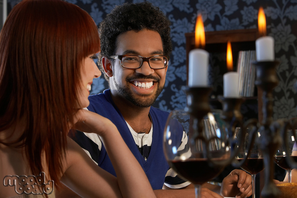 Couple laughing sitting at dining table close up