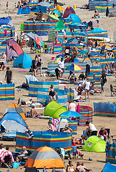 © Licensed to London News Pictures. 01/08/2019. Perranporth, UK. Beachgoers enjoy the warm weather on one of the busiest days of the year at  Perranporth beach, Cornwall. The weather in the south west is set to stay warm over the weekend, after a rainy start to the week. Photo credit : Tom Nicholson/LNP