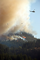 JEROME A. POLLOS/Press..Helicopters fly over a wildland fire Friday six miles west of St. Maries. The fire was reported at 3 p.m. and within four hours had grown to about 100 acres in size prompting evacuations of local residents.