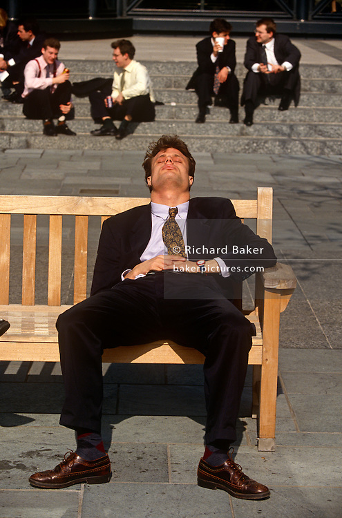 Snatching a well-earned lunchtime snooze, a young office worker in Broadgate in the City of London. The young man sits with legs wide apart, oblivious to his posture..The bench which is owned by the Corporation of London, provided in this public space for those emerging from their offices to enjoy mid-day sunshine, a chance to steal a few precious minutes sleep before re-entering their office buildings and returning to desks.