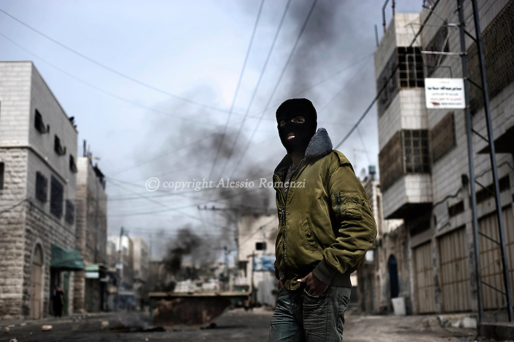HEBRON, WEST BANK - FEBRUARY 25: (ISRAEL OUT) Palestinian youths stands during clashes with Israeli soldiers on February 25, 2010 in the West Bank town of Hebron. Israeli Prime Minister Benjamin Netanyahu sparked Palestinian anger this week with his plan to include the Tomb of the Patriarchs in Hebron and Rachel's Tomb in Bethlehem in a 100-million-dollar plan to restore national heritage sites. Some 100 Palestinians clashed with Israeli troops, for a fourth consecutive day, over the mooted plans..© ALESSIO ROMENZI