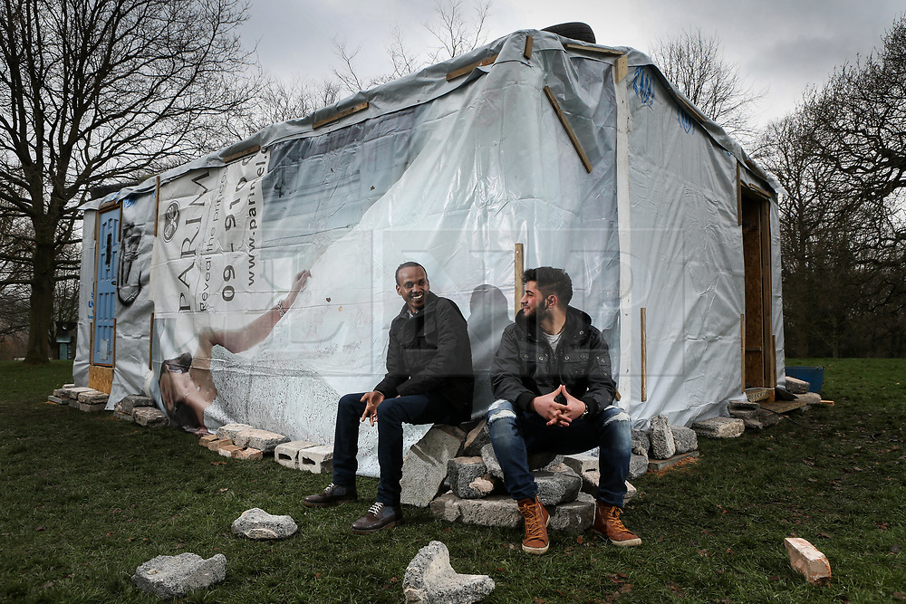 © Licensed to London News Pictures. 17/03/2017. Wakefield, UK. (L-R) Bira, aged 27 from Ethiopia, and Hassan, ages 20 from Syria, sit in front of a Syrian refugee shelter. The shelter, produced by the Amp Art collective, has been installed at the Yorkshire Sculpture Park in Wakefield, West Yorkshire. The shelter has been transported from Lebanon to the UK and is aimed at giving visitors a sense of what it is like to be a refugee. Photo credit : Ian Hinchliffe/LNP