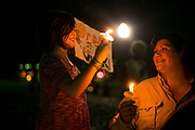 STARKVILLE, MS – FEBRUARY 1, 2017: Holdyn, 10, holds a candle with her mother Amber at a vigil honoring international students and in rejection of the travel ban is held at Mississippi State University. <br /> CREDIT: Bob Miller for The New York Times