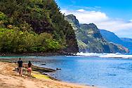 Lovers walking hand in hand alone Ke'e Beach in  Haena State Park along the Na Pali Coast.
