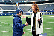 Charlotte Jones Anderson visits with a visitor on the football field at AT&T Stadium in Arlington, Texas on December 12, 2017. (Cooper Neill for The New York Times)