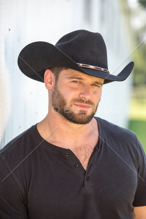 Portrait of a hot rugged cowboy by a barn