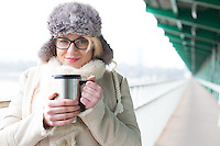 Portrait of smiling woman in warm clothing holding insulated drink container