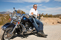 Senior man leaning on motorcycle on desert road