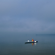 Woman in a kayak on a calm lake before the storm