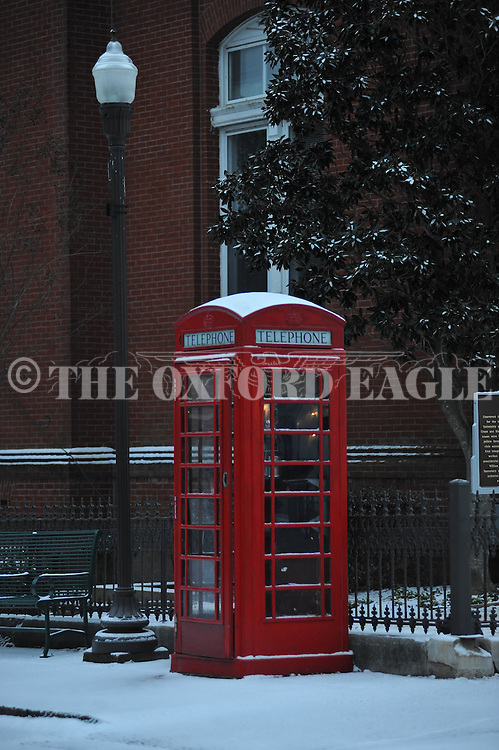 Snow surrounds the telephone booth in Oxford, Miss. on Tuesday, February 11, 2014. A thin layer of ice covered by snow has closed area schools. (AP Photo/Oxford Eagle, Bruce Newman)