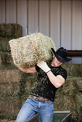 cowboy with a bale of hay over his shoulder