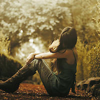 full body portrait of a young girl sitting on the ground in outdoors area.
