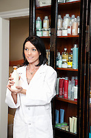 Happy beauty salon employee holding cosmetic products while looking away