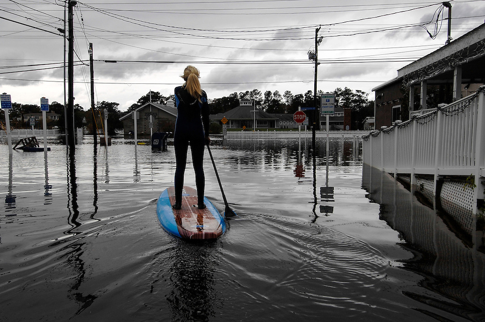 Zoe Jurusik paddle-boards down a flooded city street in the immediate aftermath of Hurricane Sandy in Bethany Beach, Delaware. Residents of the area suffered minor flooding as most of the storm surge created problems further north in New York and New Jersey.
