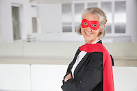 Portrait of smiling senior businesswoman in superhero costume in office