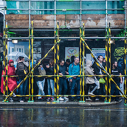 London, UK - 25 August 2014: people protect from heavy rain during the Notting Hill Carnival in London.