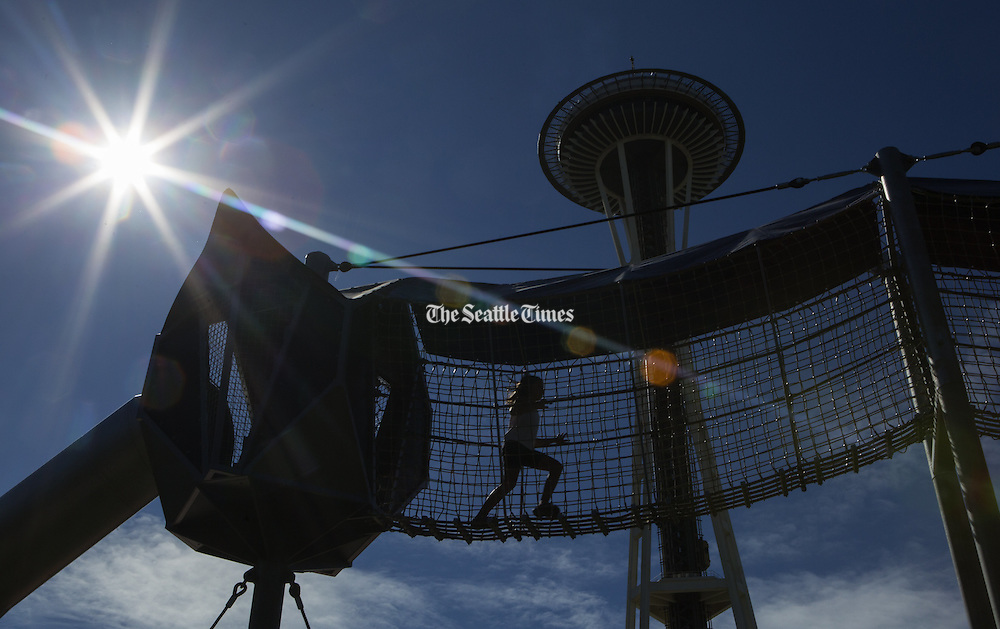 On the last day before Seattle schools finally start, a child runs on a suspended walkway away from the 38-foot long curly slide (at left) at &quot;Artists at Play,&quot; at the Seattle Center Wednesday, <br />