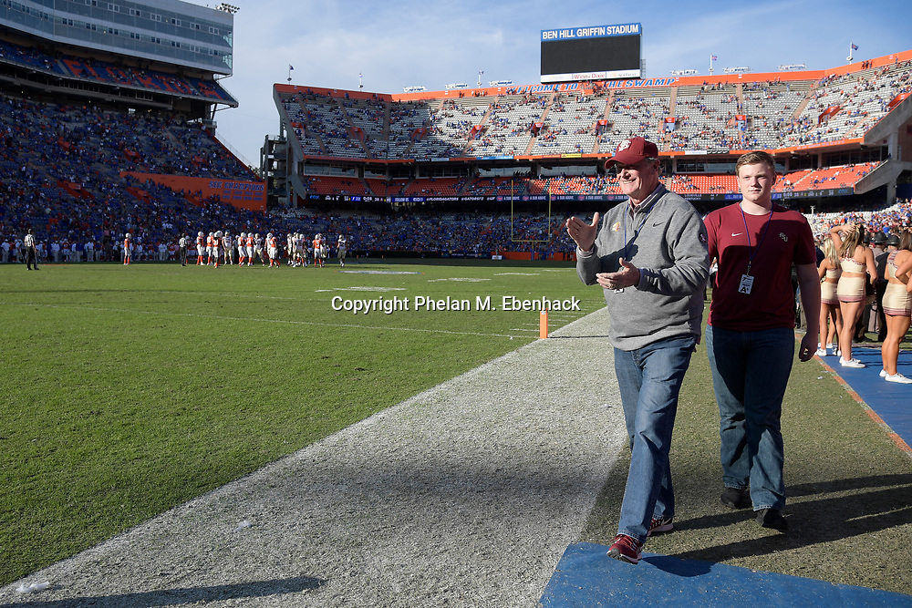 Florida State president John Thrasher applauds at the end of an NCAA college football game against Florida Saturday, Nov. 25, 2017, in Gainesville, Fla. FSU won 38-22. (Photo by Phelan M. Ebenhack)