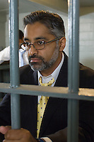 Man in spectacles behind bars