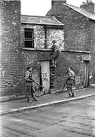 Soldier clambers over backyard wall of a house in the Markets area of Belfast. The British Army search followed the escape of internees from the prison ship Maidstone. NI Troubles. Ref: 19720119005.<br />