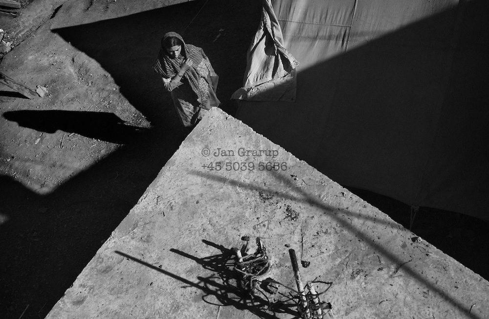 A woman in front of her tent in the village of Lamnia, on a remote mountainside. The isolated villagers here were among the last to receive emergency relief. Many weeks after the earthquake, rescue teams were finding distant villages that had not yet received help, and where survivors had died of their injuries.  Dec. 2005