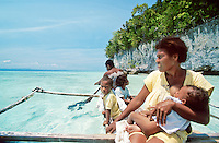 An in-canoe view of a family of five, including a mother nursing her baby, paddling their outrigger over clear blue waters in Indonesia's Raja Ampat archipelago. Experiential travel photography by Djuna Ivereigh.