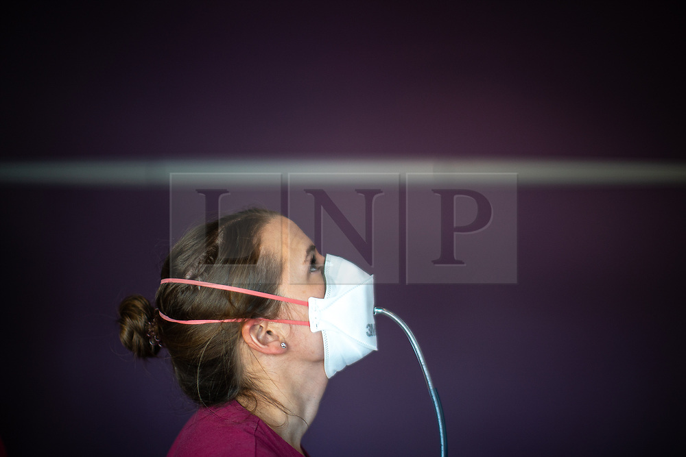 © Licensed to London News Pictures . 21/05/2020 . Manchester , UK . Principal Radiographer at the Proton Beam Therapy Centre JANE MILLER (37 from Poynton) cranes her neck upwards during fit-testing for an FFP3 mask , using specialised equipment that measures the performance of each of three different mask shapes on wearers' faces to identify the safest fit . Due to the Covid-19 outbreak , fit testing has been scaled up by the hospital , in an effort to provide more effective protection for as many staff as possible . Specialist cancer centre , The Christie Hospital , is adapting in order to ensure the safety of patients and staff . They are reporting a drop in referrals during the UK's Coronavirus lockdown and there is concern that cancers are going undiagnosed and untreated . Photo credit : Joel Goodman/LNP