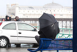 © Licensed to London News Pictures. 14/09/2015. Brighton, UK. A man shelters under his umbrella. Brighton and the South Coast is being battered by strong winds and powerful waves. Today September 14th 2015. Photo credit : Hugo Michiels/LNP