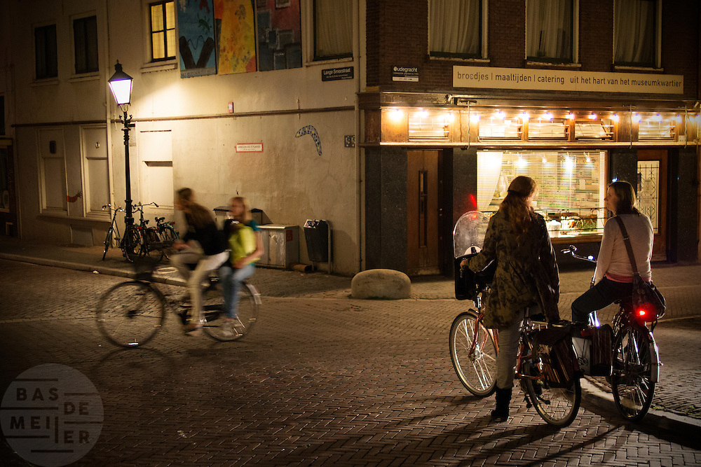 Op de Oudegracht in Utrecht praten twee vrouwen 's avonds laat nog even met elkaar op de fiets voor ze afscheid nemen. Ondertussen rijden een fietser met iemand achterop voorbij.<br />
