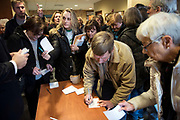 PEWAUKEE, WI-FEB. 11, 2017: Citizens swarm to check in before Rep. Jim Sensenbrenner's town hall meeting at the Pewaukee Public Library in Pewaukee, WI Sat. Feb. 11, 2017. The room hit max capacity and the overflow of people waited in the building's lobby. Lauren Justice for The New York Times