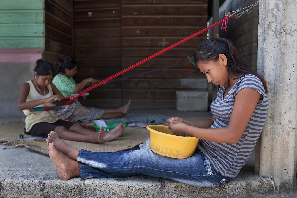 Maria Uscap Iboy (background), 43, weaves at home along with her daughter Maria Florinda Lajuj Uscap, 19, while her other daughter Morelia Suzana Lajul Uscap, 15, peels pumpkin seeds. They live in the community of Pacux, where the former Achi Mayan residents of Rio Negro were resettled after the destruction of their village, numerous massacres, and flooding of the Chixoy river basin. Uscap Iboy survived the March 13, 1982, massacre at Pak'oxom along with her brother Juan as they, along with 16 other children, were taken as child slaves by civil patrolmen from Xococ. She remained in custody for two years before she reunited with community members from Rio Negro. Pacux, originally planned as a so-called model village where they army would resettle civilians from areas controlled by the guerrillas, lies in the outskirts of Rabinal city. It is plagued today by poverty and crime as the citizens of Pacux are still outcast as former guerrillas by large sectors in Rabinal. Pacux, Rabinal, Baja Verapaz, Guatemala. July 16, 2014.