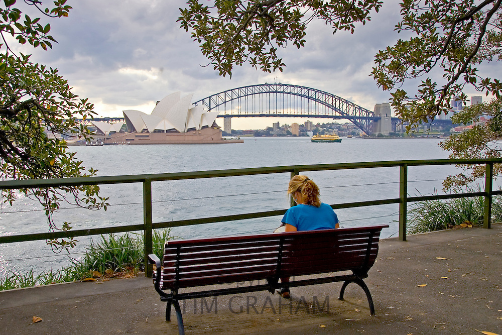 Woman views Sydney Opera House and Harbour Bridge from bench across the bay, Australia